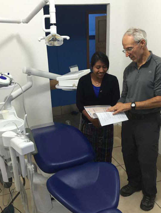 Juana learns dental treatment techniques from a visiting dentist