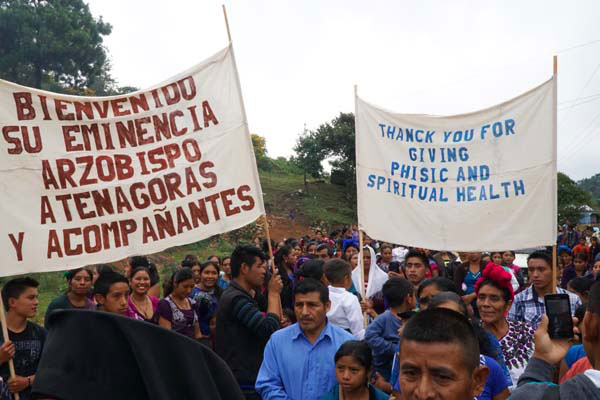 "At the blessing of the clinic, people carried a sign saying ""Thank you for giving us physic[al] and spiritual health."""