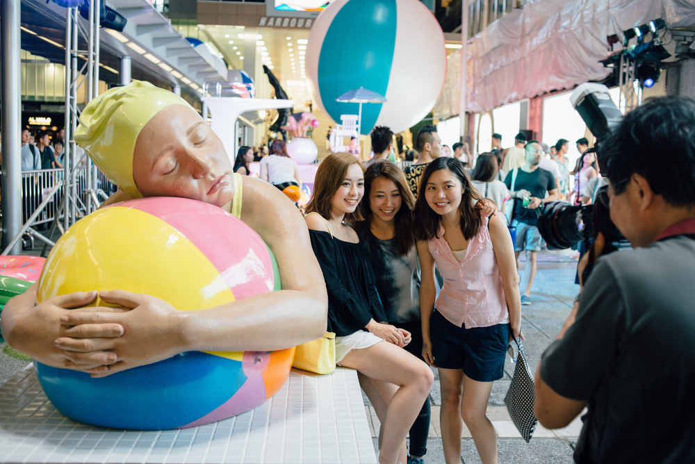 Fans pose by Feuerman's  Brooke With Beach Ball  during the poolside party celebrating the exhibition.