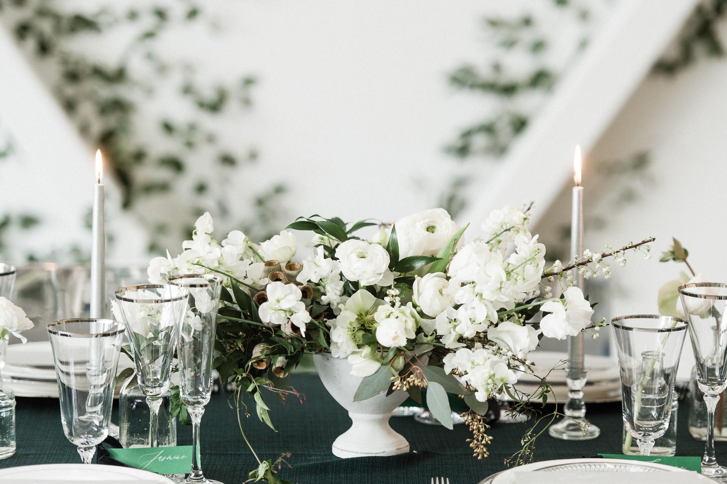 Artists for humanity epicenter wedding | Boston wedding | modern white floral centerpiece and bud vases by Twig & Briar | green botanical wedding inspiration | candles and ivy feature wall
