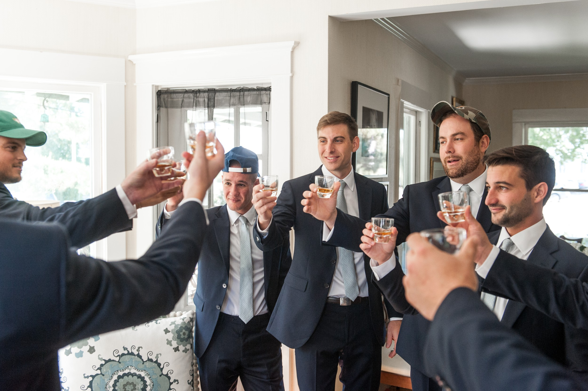 Wee Burn Beach Club Wedding Darien CT groom and groomsmen toasting during getting ready for fall wedding on shoreline in New England