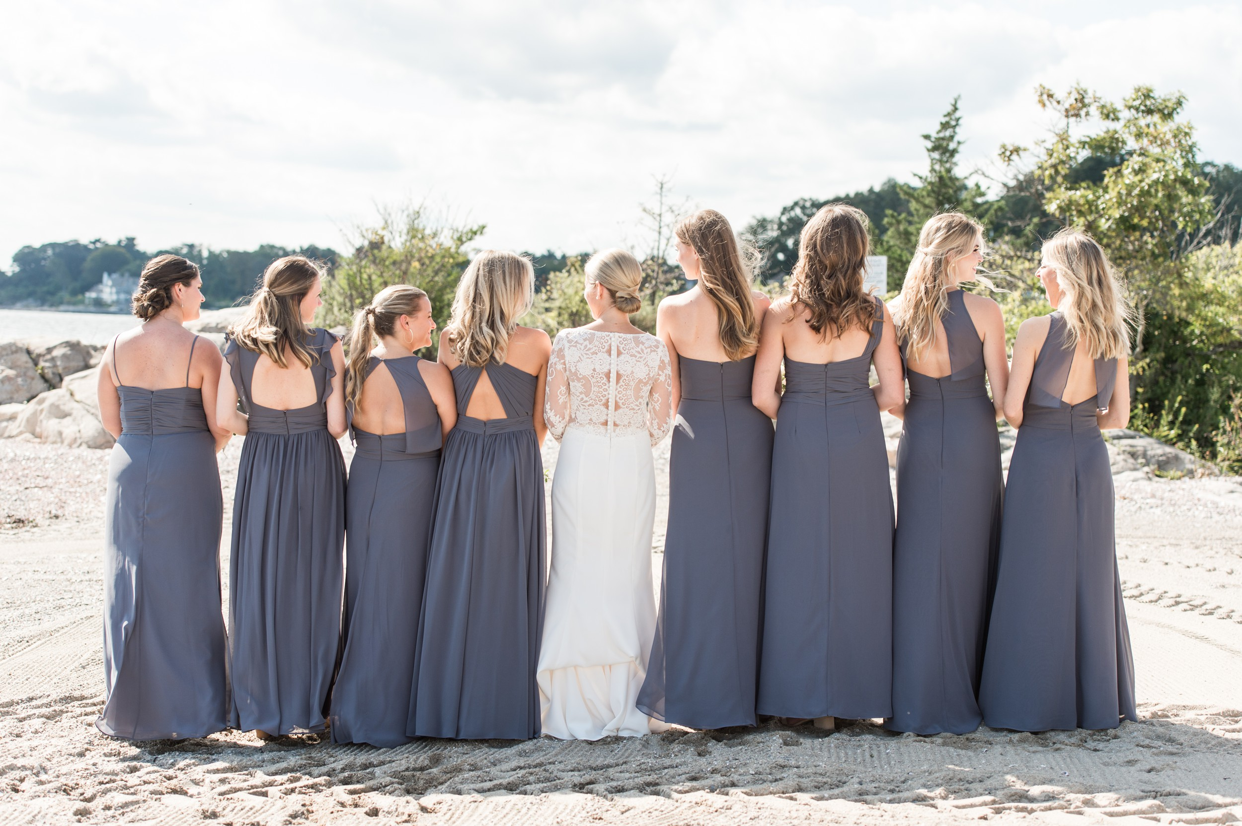 Sunny Wee Burn Beach Club Wedding Darien CT Bridal Portraits on the Beach with bridesmaids in gray Hayley Paige bridesmaids dresses and Bride in Lace Amsale Dress, Low Bun, and White Florals