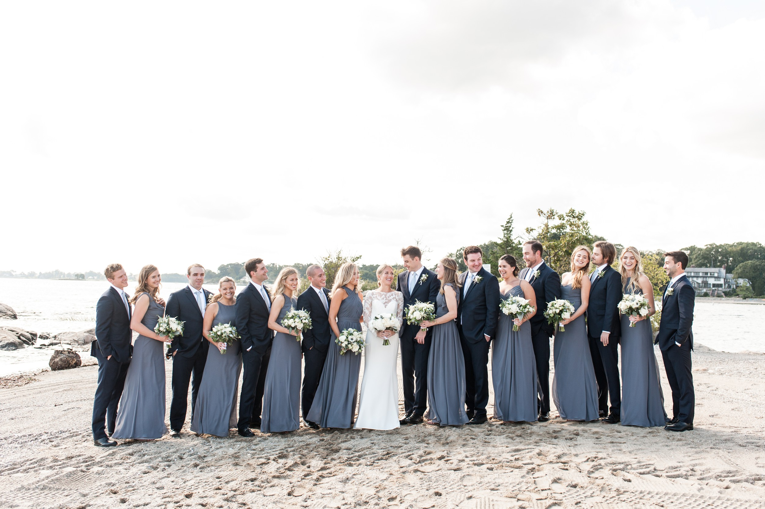 Sunny Wee Burn Beach Club Wedding Darien CT Bridal Party Portraits on the Beach with gray Hayley Paige bridesmaids dresses and Groomsmen in Navy Suits and Gray Ties