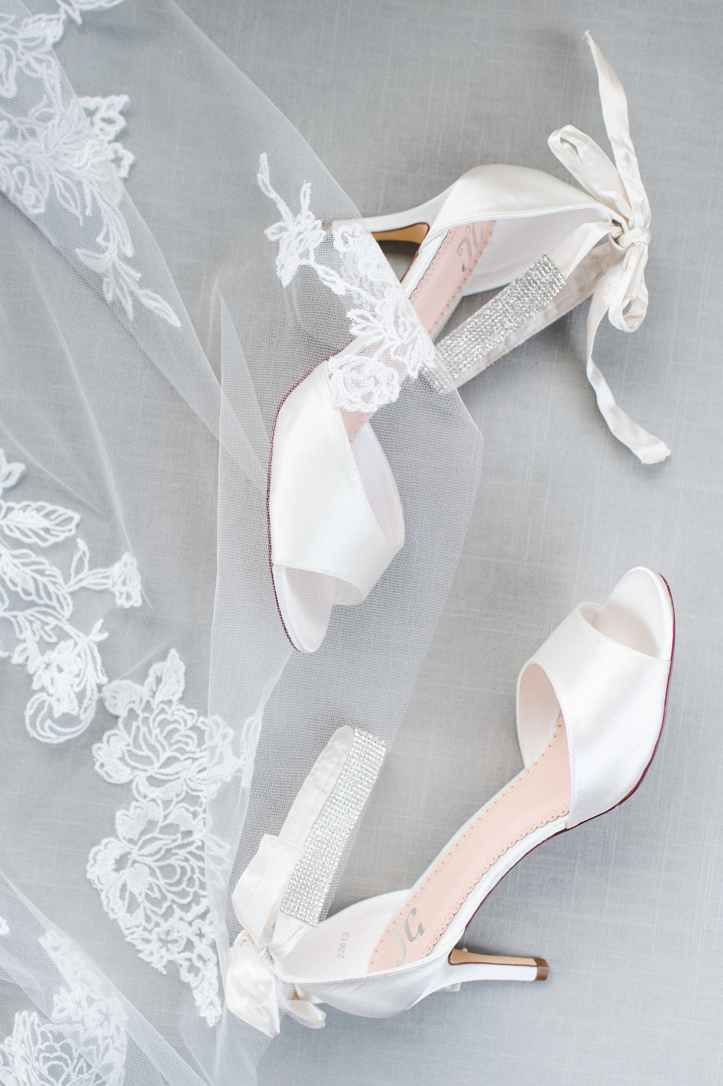 The Villa at Ridder Country Club Spring Wedding East Bridgewater MA bridal details flat lay white wedge wedding shoes and lace veil
