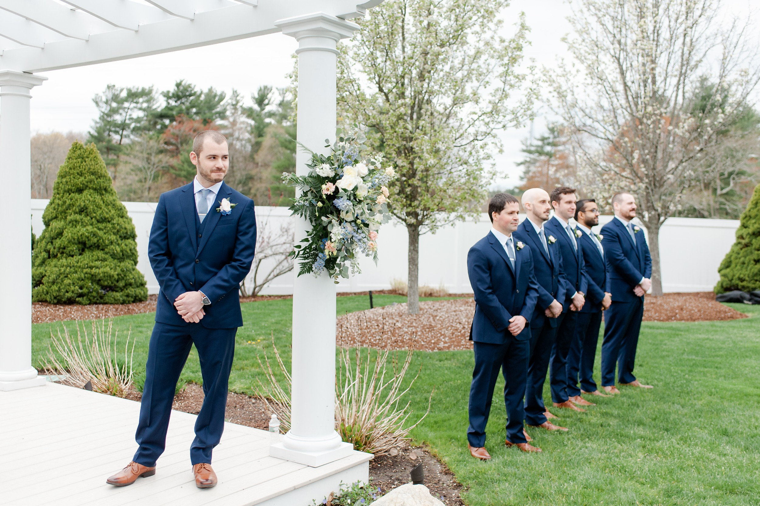 The Villa at Ridder Country Club Outdoor Wedding Ceremony in Spring with asymmetrical floral ceremony backdrop