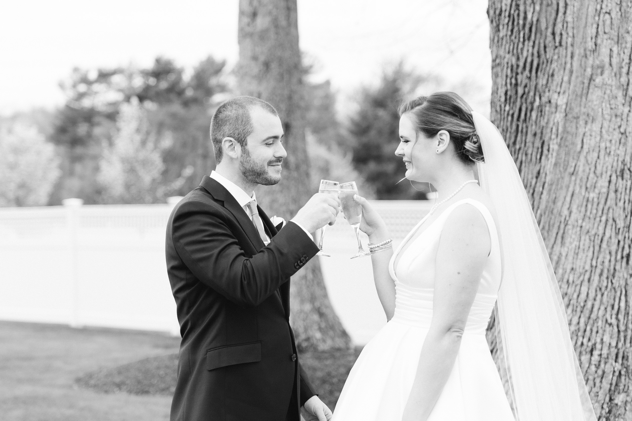 The Villa at Ridder Country Club Outdoor Wedding Ceremony the newlyweds toast with champagne black and white wedding photo