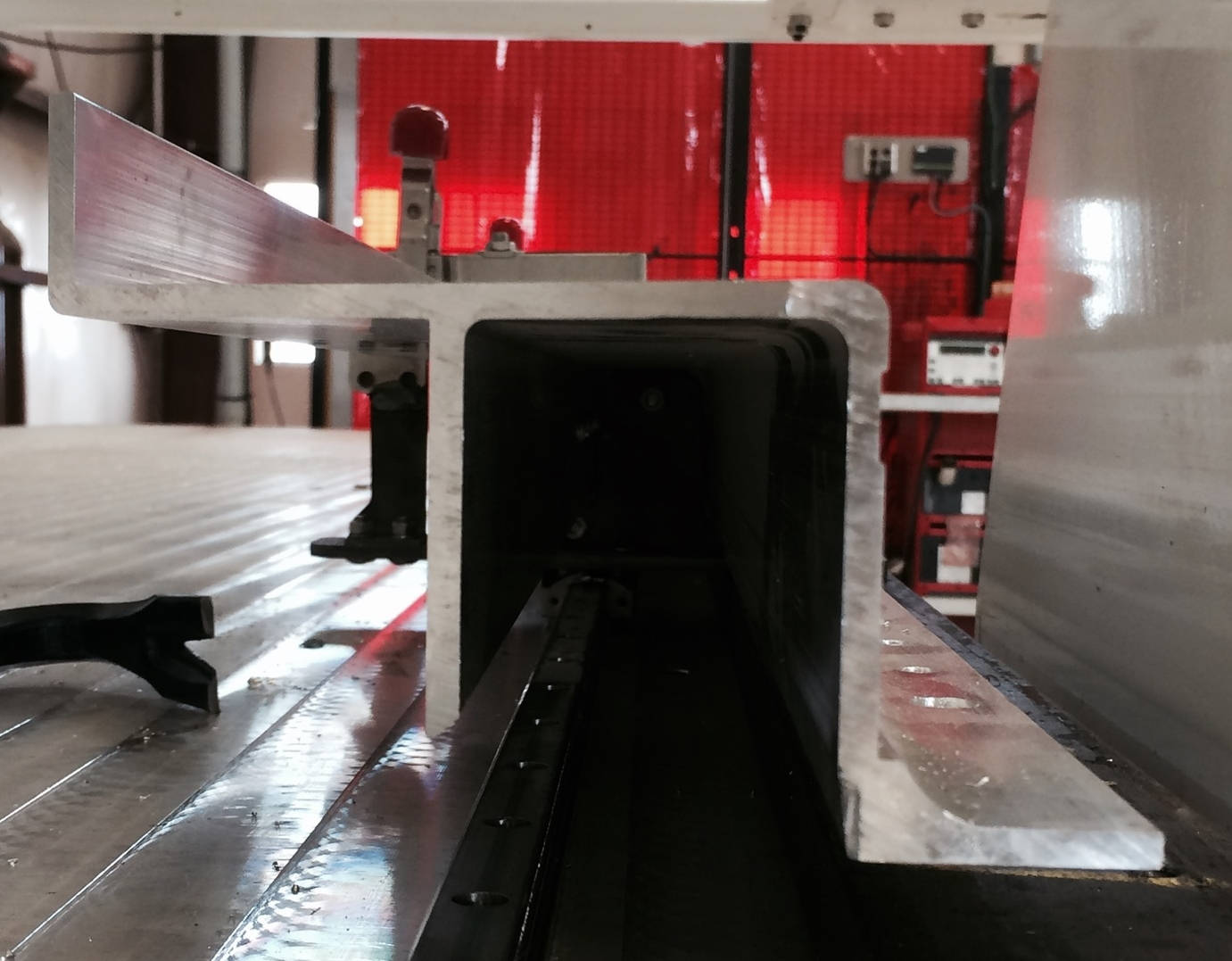 Here is an end view of a typical aluminum extrusion. Both drilling and cutting operations need to be performed on the top and sides of the part which takes several set-ups on traditional milling machines but only one set-up on our new machine.