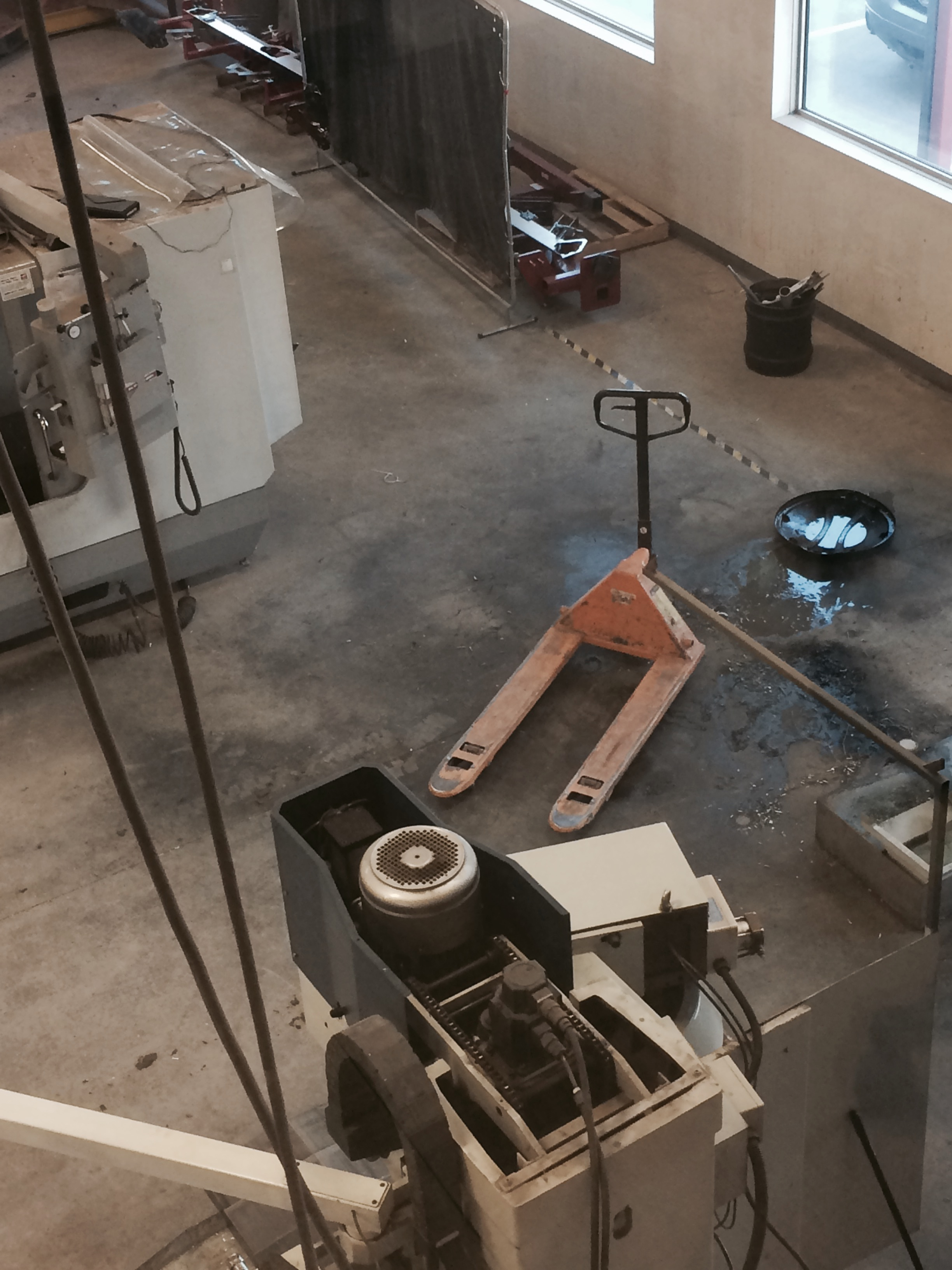 This is an embarrassing picture of the mess under our machining center. After a few years of coolant and oil making it's way to the floor the concrete has becoming so stained it was impossible to clean anymore.