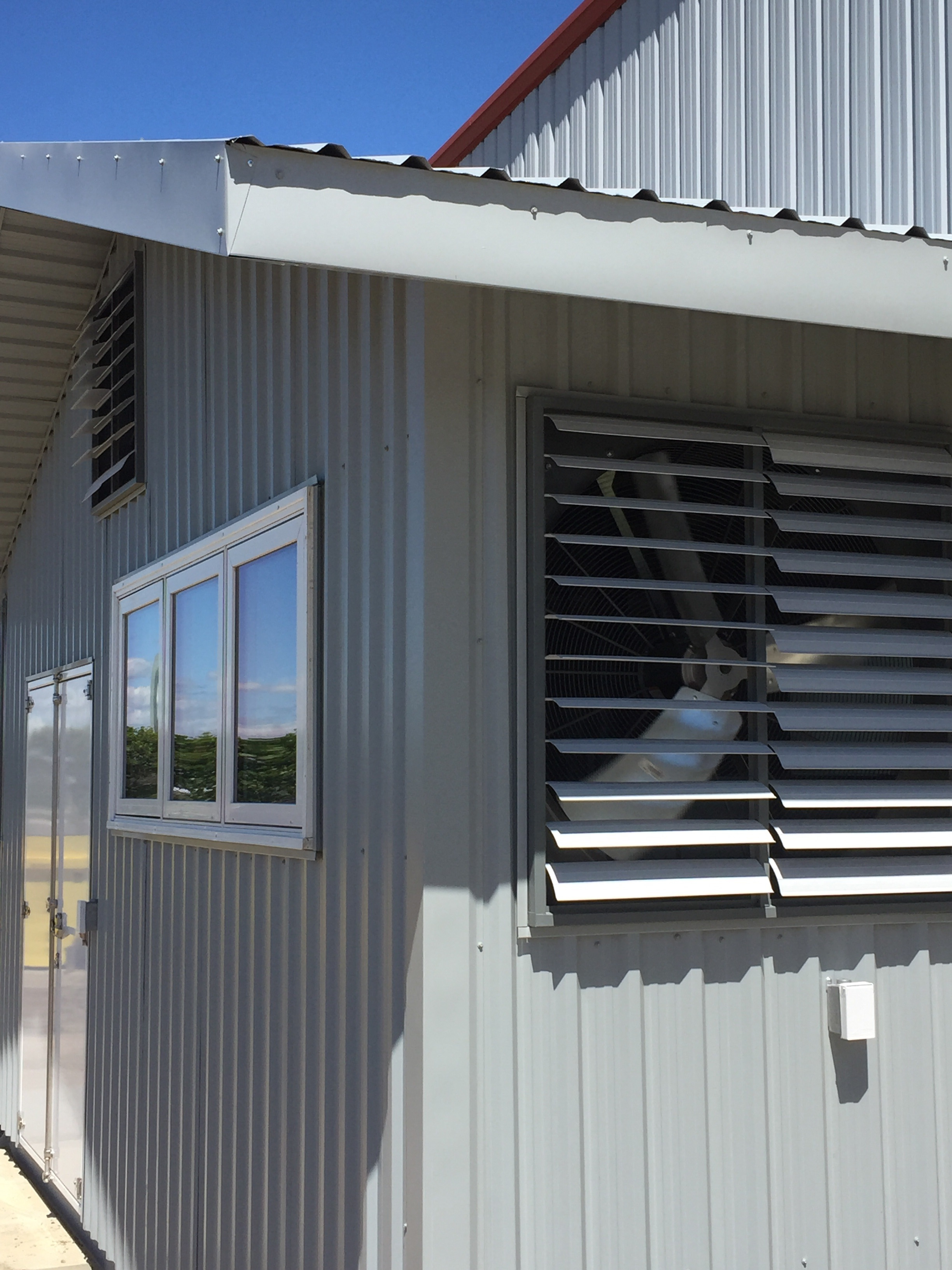 Outside the south wall, you can see the flaps open for both one large exhaust fan and the gable fan. As a side note, the white entry doors (left side of picture) were also manufactured in house at Lean Machine!