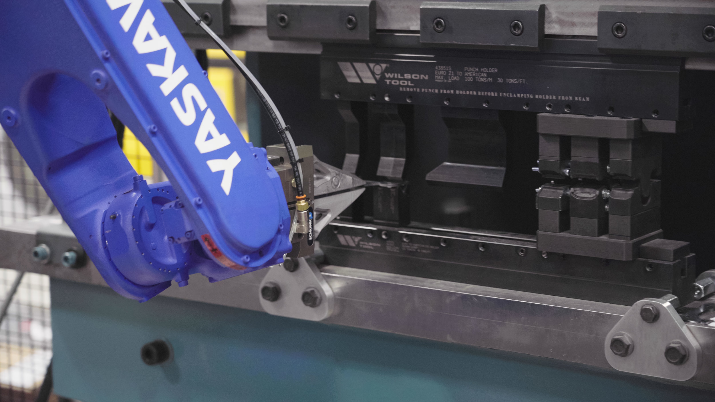 "The robot is putting a part into the punch and die set for bending. The Wilson tooling is made at an angle that bending past 90 degrees is possible without changing to ""stamping"" in the tools."