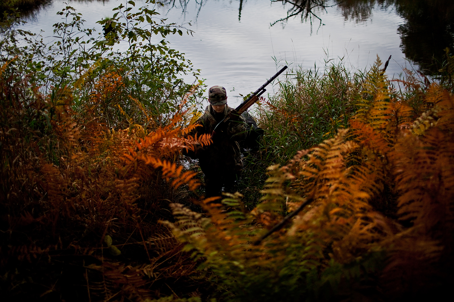 Isaac Eisch climbs out of the pond while duck hunting with their uncle in Wautoma, Wis. Thanks to their uncle, the brothers are introduced to a routined schedule and are kept busy with outdoor activities, while their father is deployed in Afghanistan.
