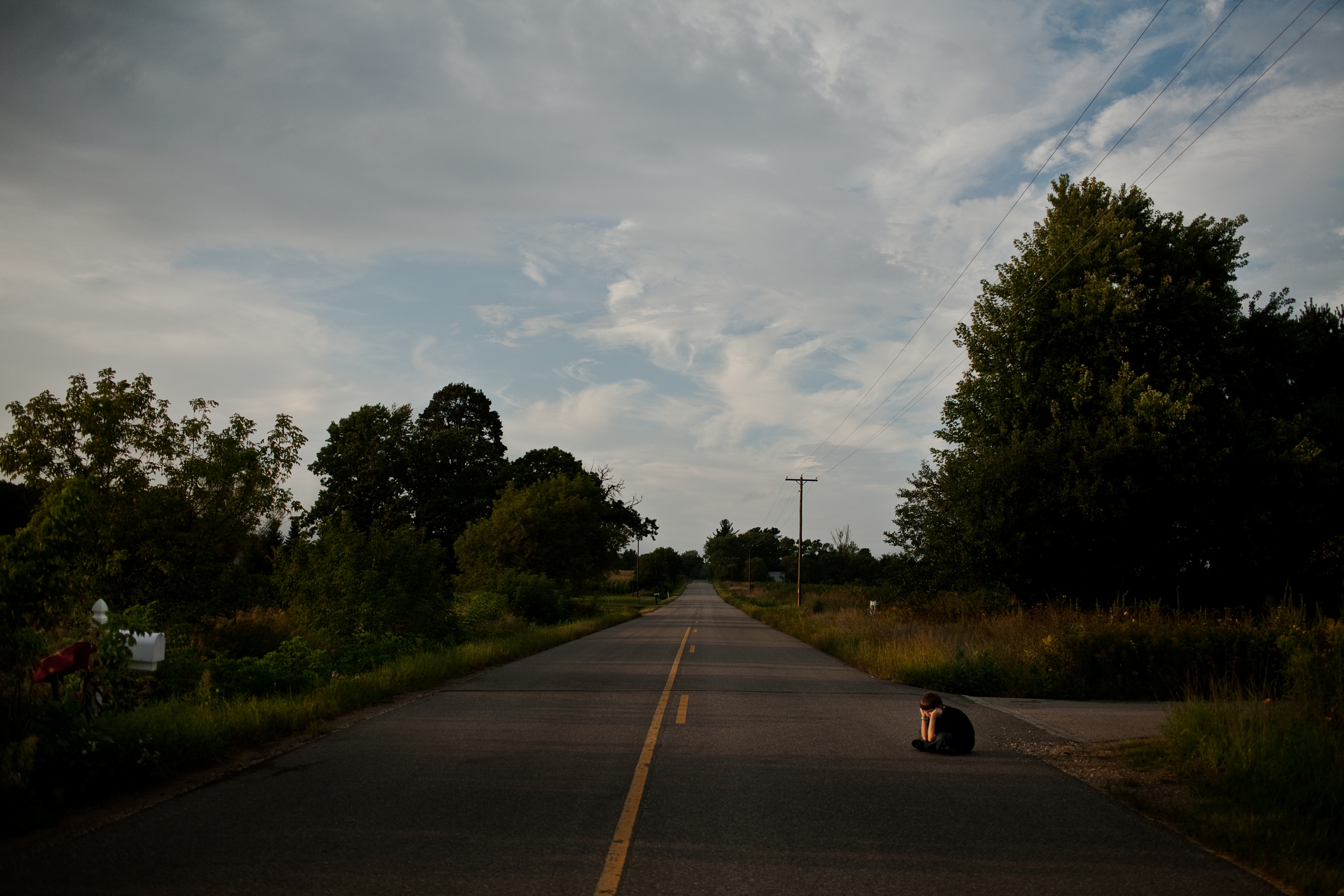 Isaac sits alone, outside his uncle's house as the sun sets over the wide open road.