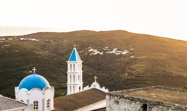 Φωτογραφία εκκλησίας στην Τήνο, με πράσινα λιβάδια στο βάθος την ώρα του ηλιοβασιλέματος.