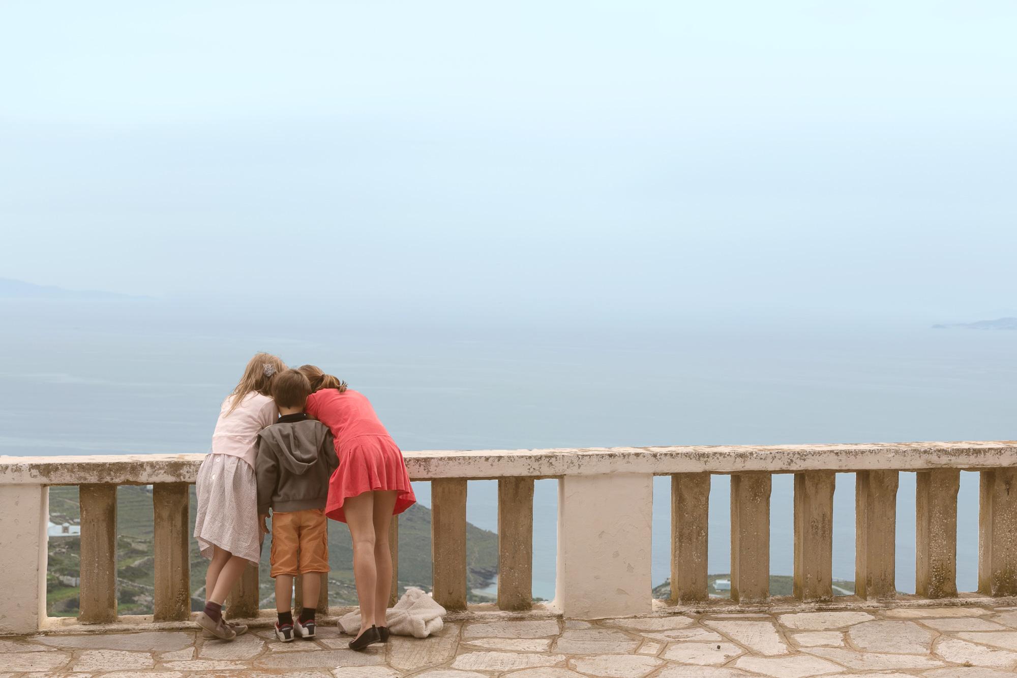 Τρια παιδιά κοιτούν κάτι με μεγάλη περιέργεια στην Τήνο το Πάσχα.
