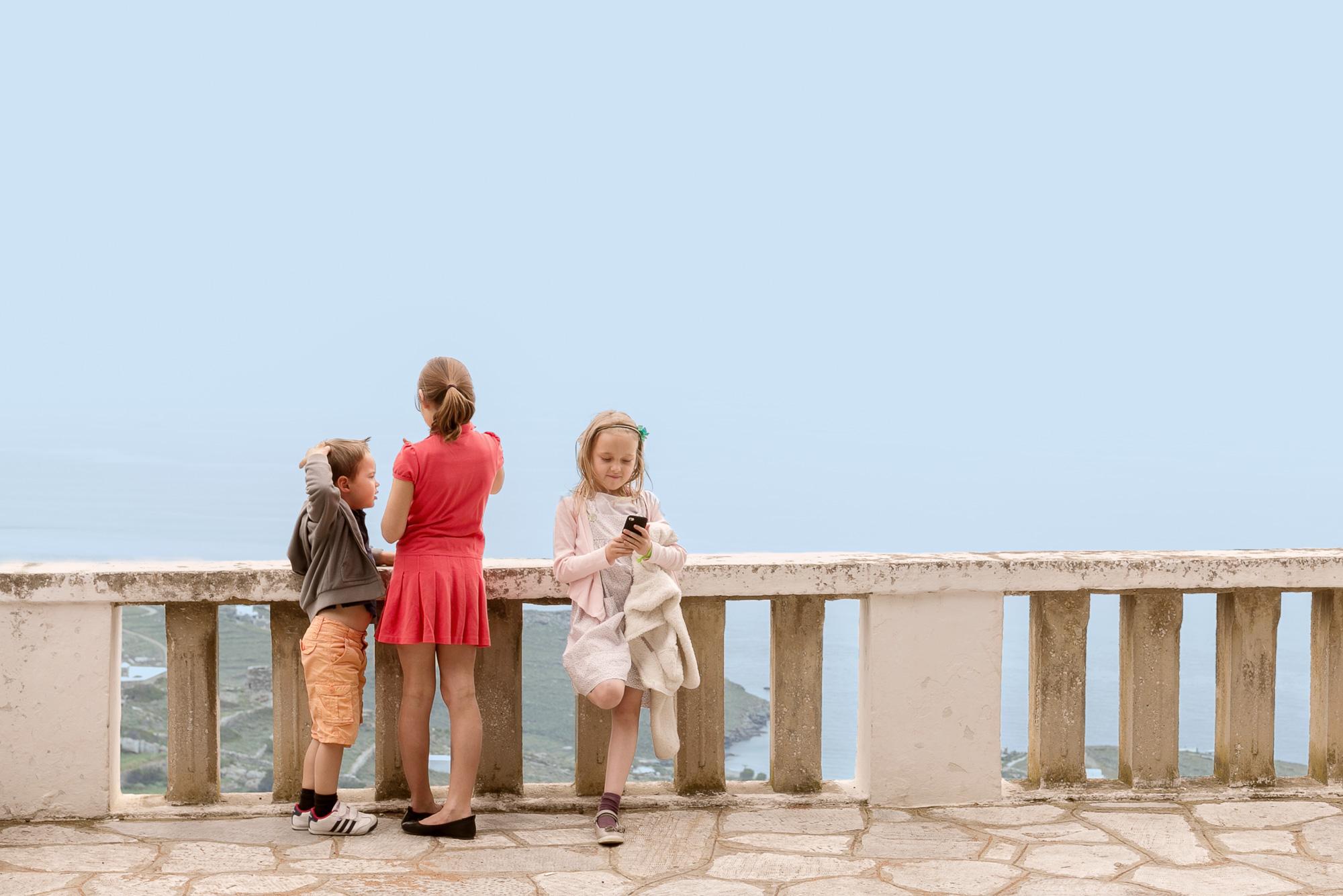 Τρια μικρά παιδιά παίζουν σε πλατεία της Τήνου.