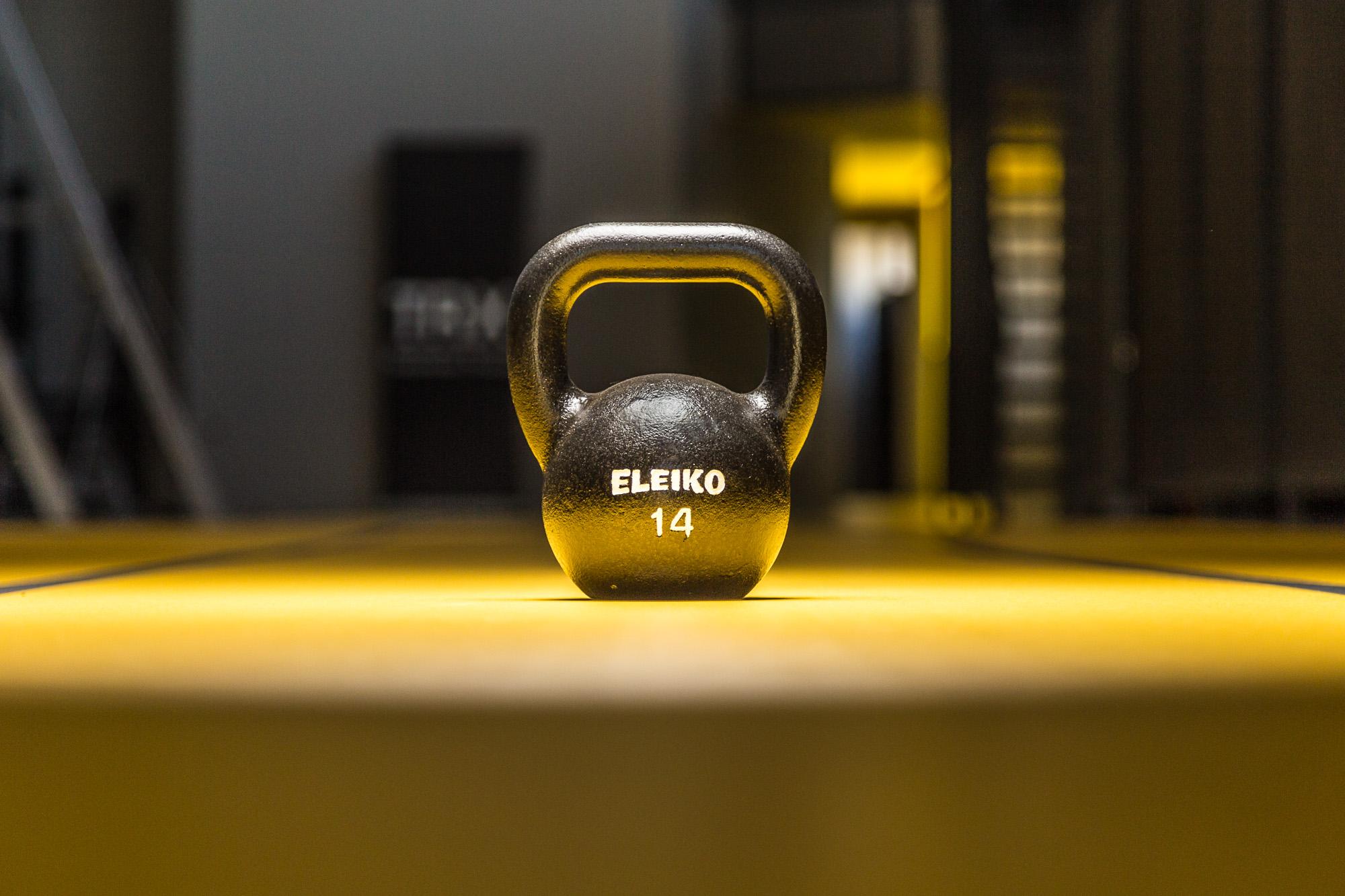 Φωτογράφιση εξοπλισμού του γυμναστηρίου, μαύρο βαράκι σε κίτρινο δάπεδο, φωτογραφημένο με φλας.