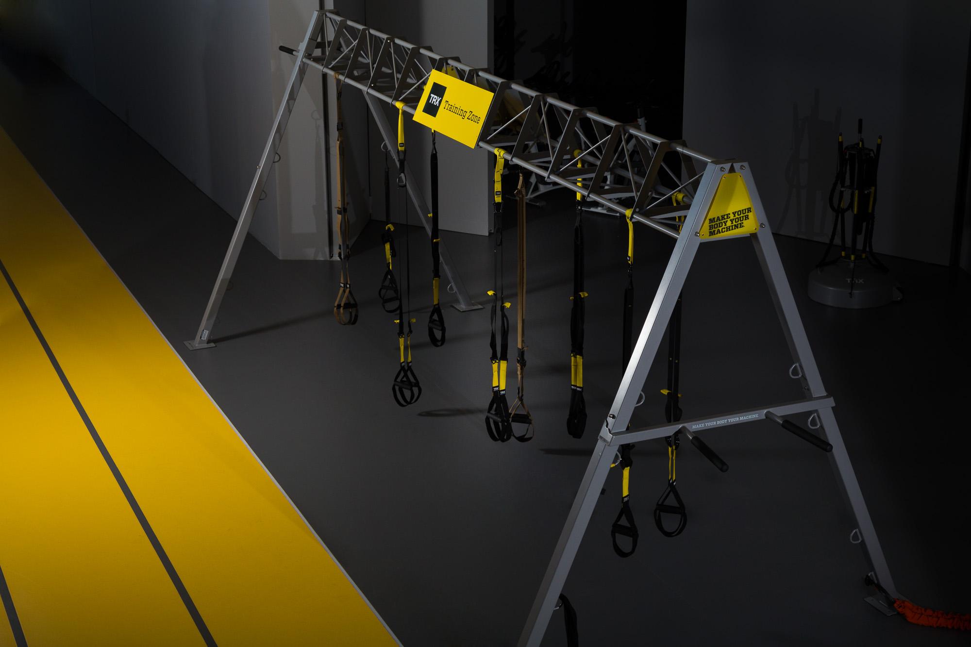 Φωτογράφιση του βασικού εξοπλισμού TRX με τους ιμάντες και την σιδερένια κατασκευή. Φωτογραφία τραβηγμένη με τεχνητό φως.
