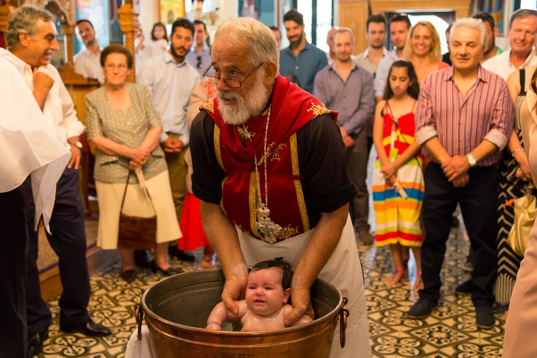 Φωτογραφία του παπά καθώς κρατάει το μωρό μέσα στην κολυμπήθρα.