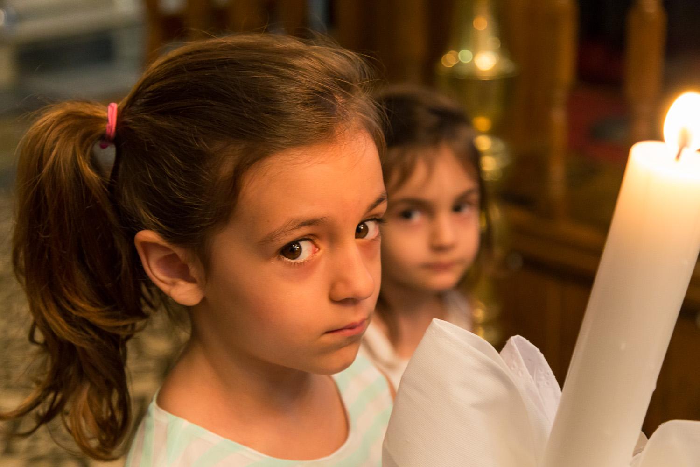 κοντινό πορτραίτο κοριτσιού που κρατάει μια λαμπάδα μέσα στην εκκλησία.