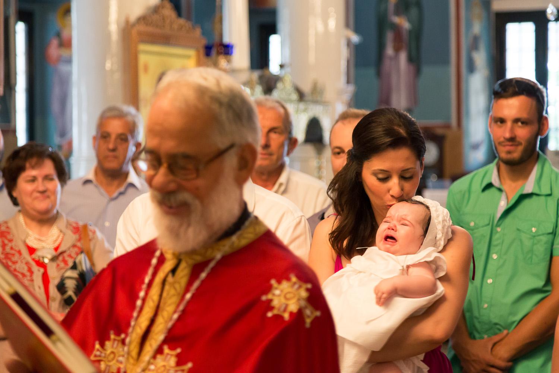 Φωτογραφία μωρού που κλαίει στην αγκαλιά της νονάς της μέσα στην εκκλησία στην Πορταριά.