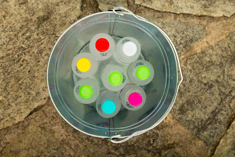 Φωτογραφία κάτοψης ενός μεταλλικού κουβά γεμάτου με μικρά μπουκαλάκια νερού με πολύχρωμα καπάκια.