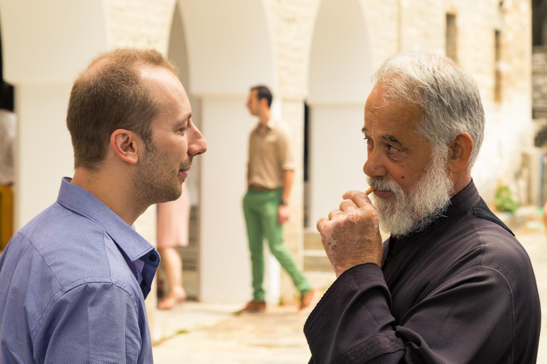 O Βαγγέλης Κανέλης μιλάει με τον παπά της εκκλησίας λίγο μετά τη βάφτιση της Αναστασίας στην Πορταριά.