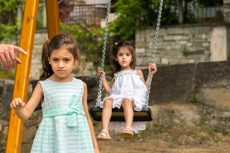 Φωτογραφία δύο μικρών κοριτσιών που παίζουν στις κούνιες καθώς ο πατέρας τους τους λέει ότι πρέπει να φύγουν.