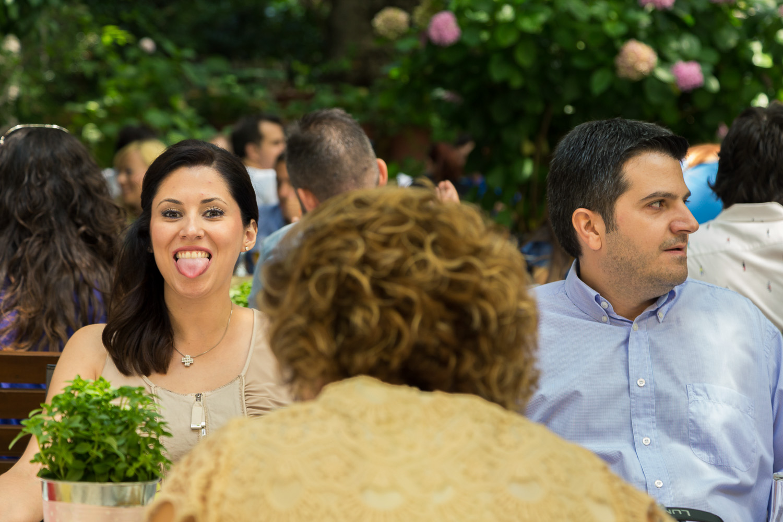 Η νονά βγάζει τη γλώσσα κοροϊδευτικά στο γιορτινό τραπέζι της βάφτισης.
