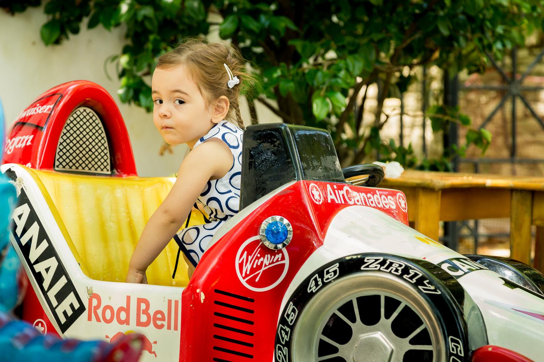 Φωτογραφία κοριτσιού που παίζει με ένα αυτοκινητο της φόρμουλα 1.