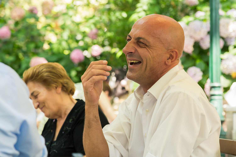 Πορτραίτο άνδρα, καλεσμένου στο γιορτινό τραπέζι που γελάει.