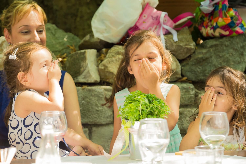 Τρια μικρά κορίτσια μυρίζουν βασιλικό στις χούφτες τους.