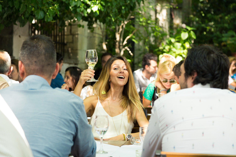 Φωτογραφία νεαρής κοπέλας στο γιορτινό τραπέζι που προτείνει το ποτήρι της χαρούμενη.