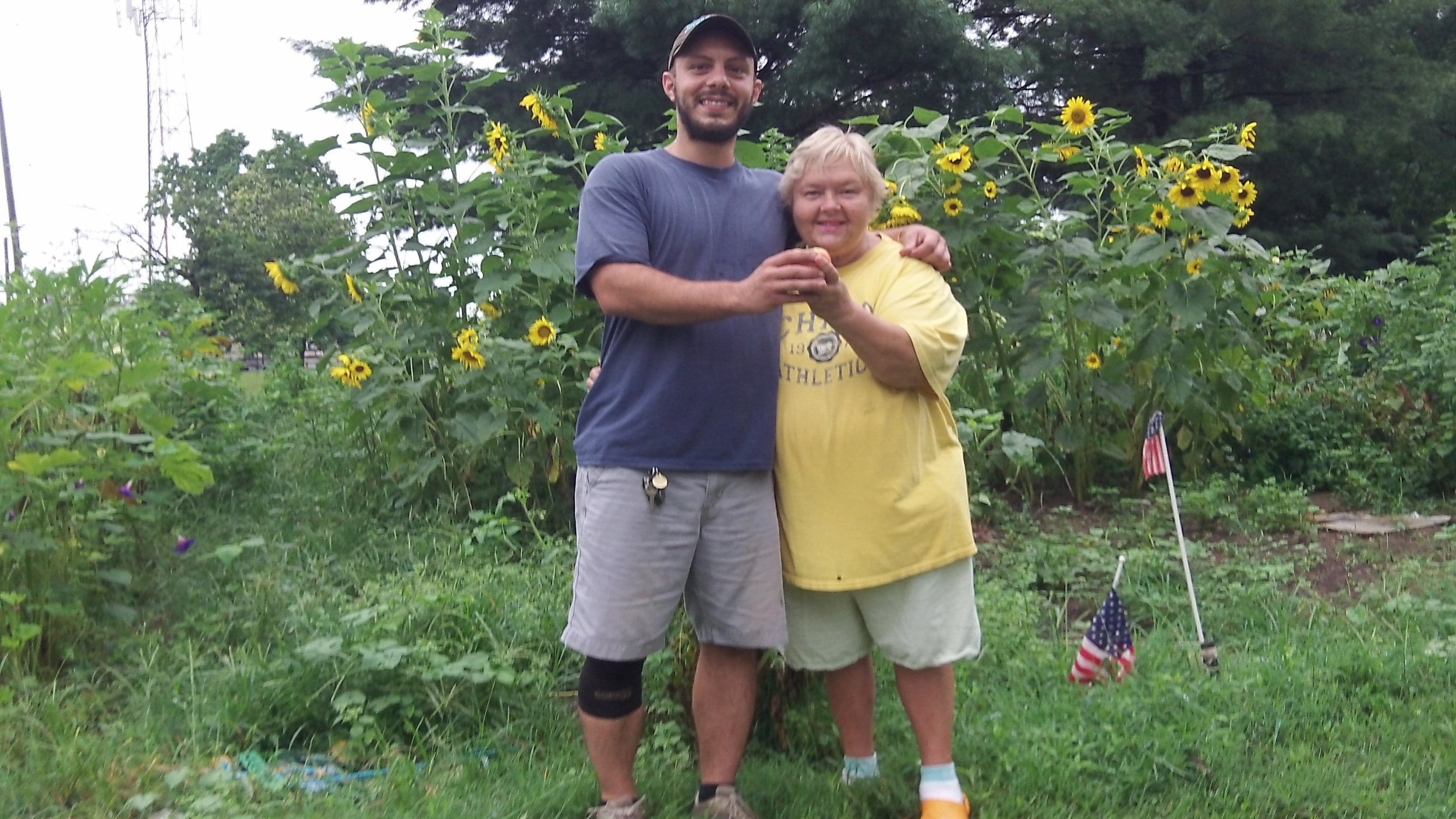 IMAGE DESCRIPTION:  Two people stand in front of a community garden and small sunflower patch. They each have an arm around the other, and with their other hands are together holding out an obscured piece of produce.