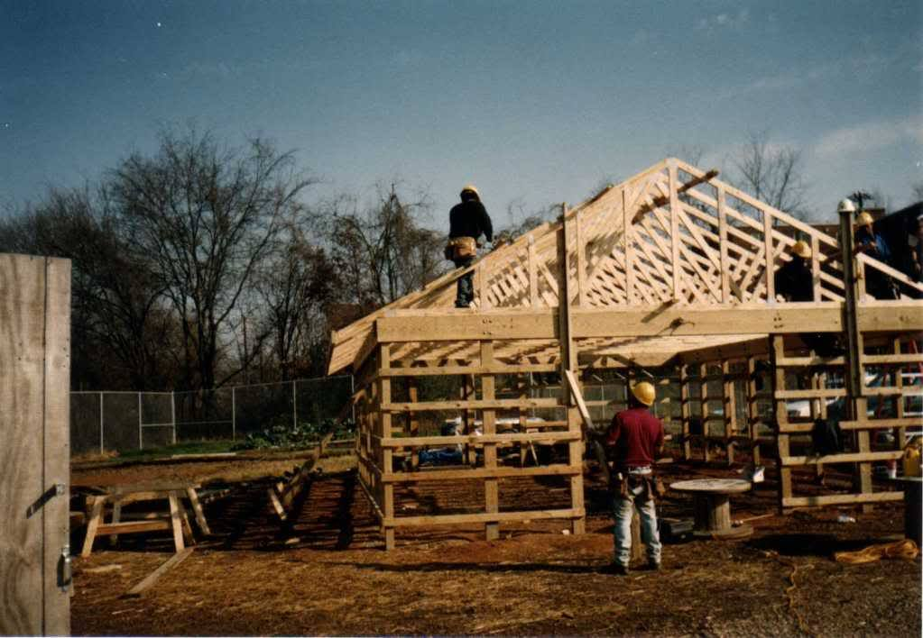 IMAGE DESCRIPTION:  A photo from the late 1990s showing people working on Beardsley Farm's barn. There are three people wearing hard hats putting up the wooden frame and wall studs of the barn.