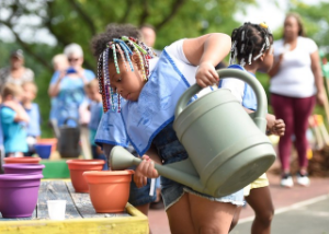 IMAGE DESCRIPTION:  A child watering a ceramic pot.