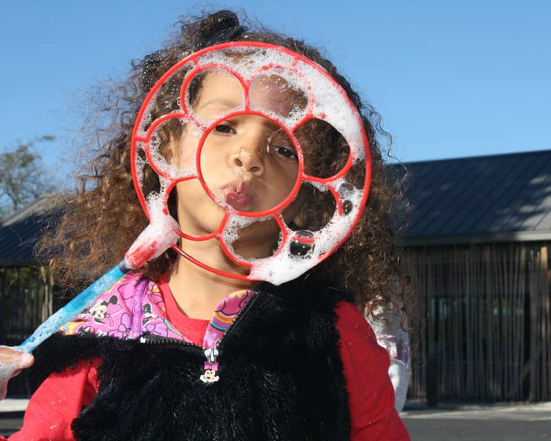 IMAGE DESCRIPTION:  A child with curly hair blowing bubbles in front of Beardsley's Education Center.