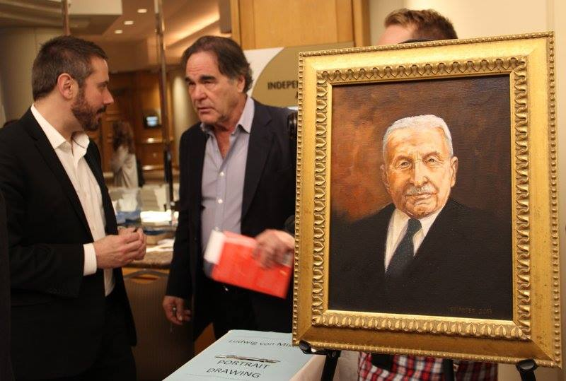 An unexpected juxtaposition. Oliver Stone and documentarian Jeremy Scahill chat behind a painting of the great libertarian economist Ludwig von Mises at the International Students for LIberty Conference. Source: Sheldon Richman's Facebook account.