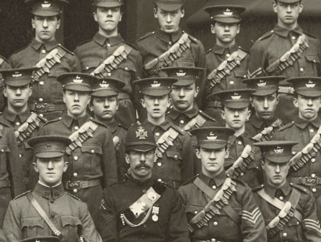 """Source: Governors of the Schools of King Edward VI in Birmingham, via  John Garth  . Garth's caption: """"A face in the crowd: Tolkien, fourth from left in the middle row, stands for inspection with the new Cadet Corps at King Edward's School, Birmingham, on 4 April 1907"""""""