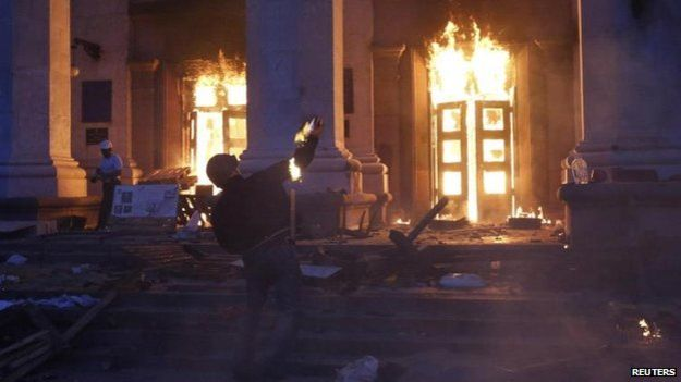 A man throwing a petrol bomb at the Trades Union House in Odessa.