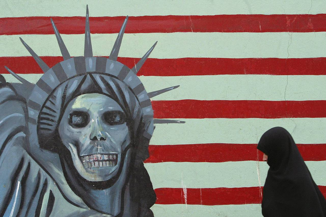 An Iranian woman wearing a hijab walks by an anti-American painting on the former US embassy in Tehran.