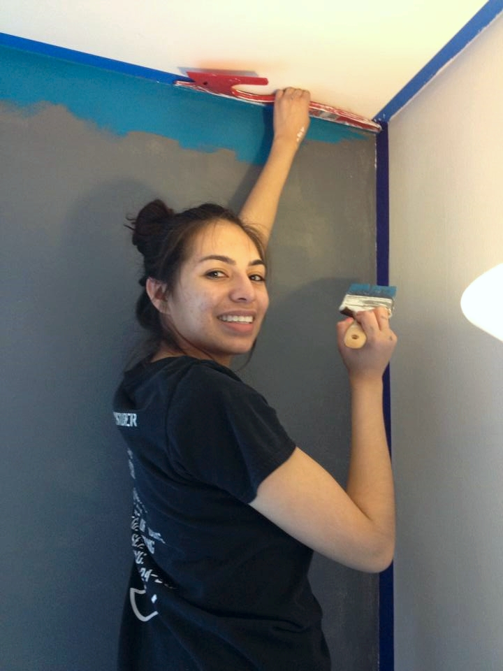 Using a paint shield, Joanna is able to block the blue paint from seeping under the tape and onto the bright white ceiling.
