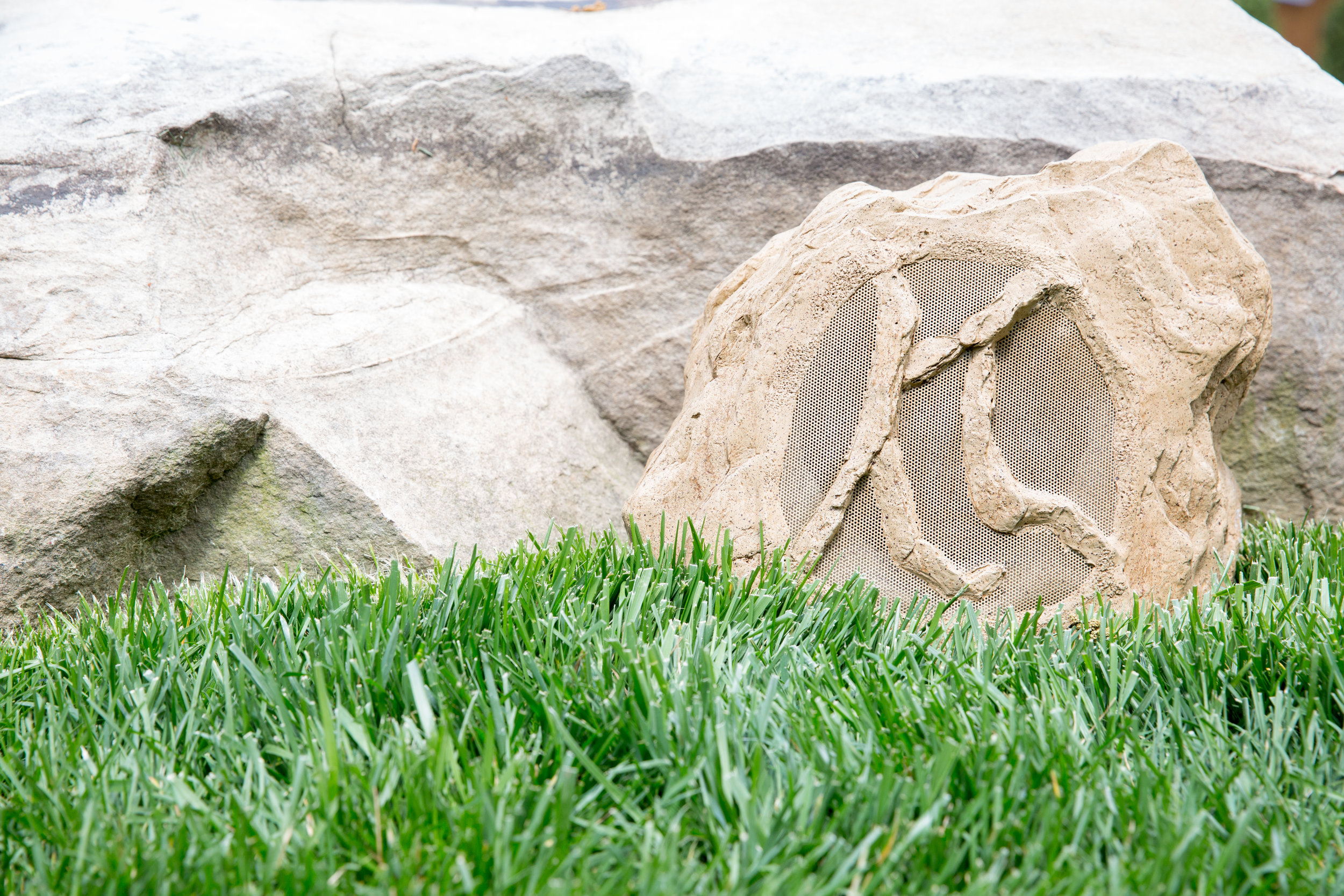 Rock speakers can be color matched to the landscape and are easily hidden by planting
