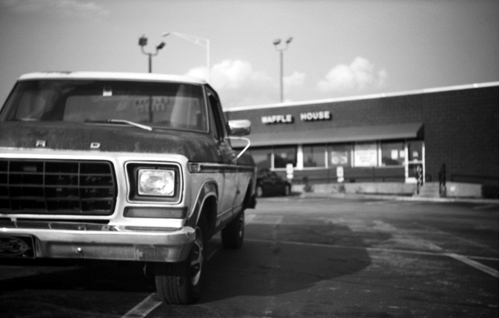 I shot this photo in 2012, using a vintage camera made circa 1938.  The choice of the old truck as the subject, the soft focus and use of black & white film all help cultivate a feeling of age.  By shooting from a low vantage point, I made the truck stand out dramatically in front of the restaurant.  And that's before I even brought it into Photoshop.