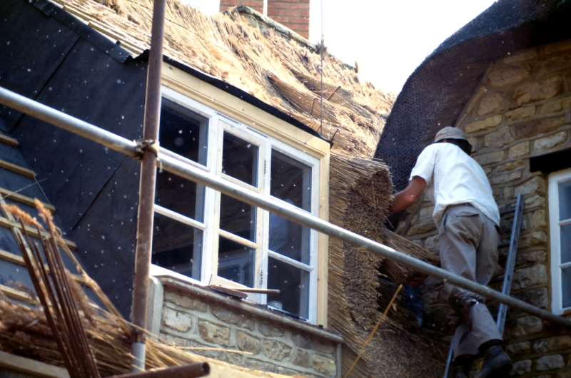 Man repairing a thatched roof somewhere in England (1992). I like how the sunlight reflected off the flying bits of hay as he worked.  Candid photos of everyday people working are among my favorite subjects.