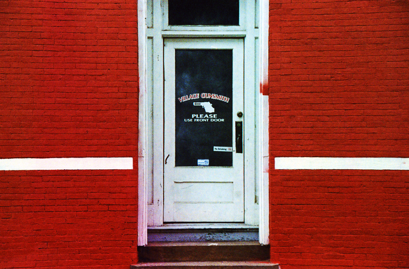 Sometimes I find more interesting subjects in alleys than I do on Main Street, like this gun shop side entrance. The white lines added visual interest by breaking up the solid red.