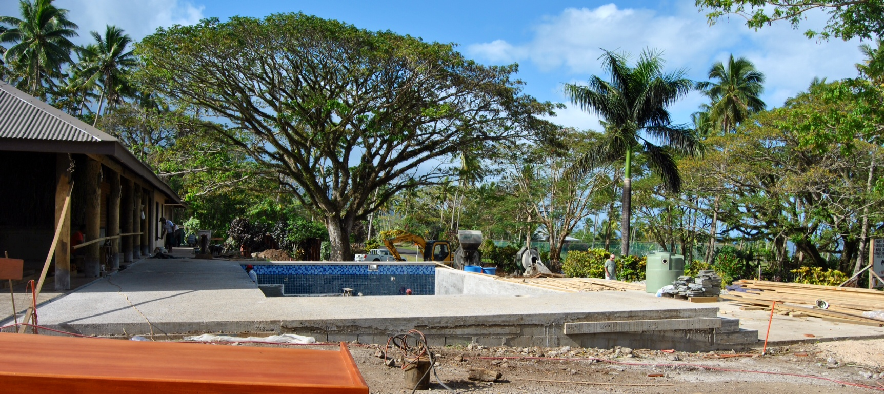 This is looking south from just outside Bure No. 1. In the foreground, our contractors are working on bed frames for the rooms. You can see a couple craftsmen working on tiling the pool.