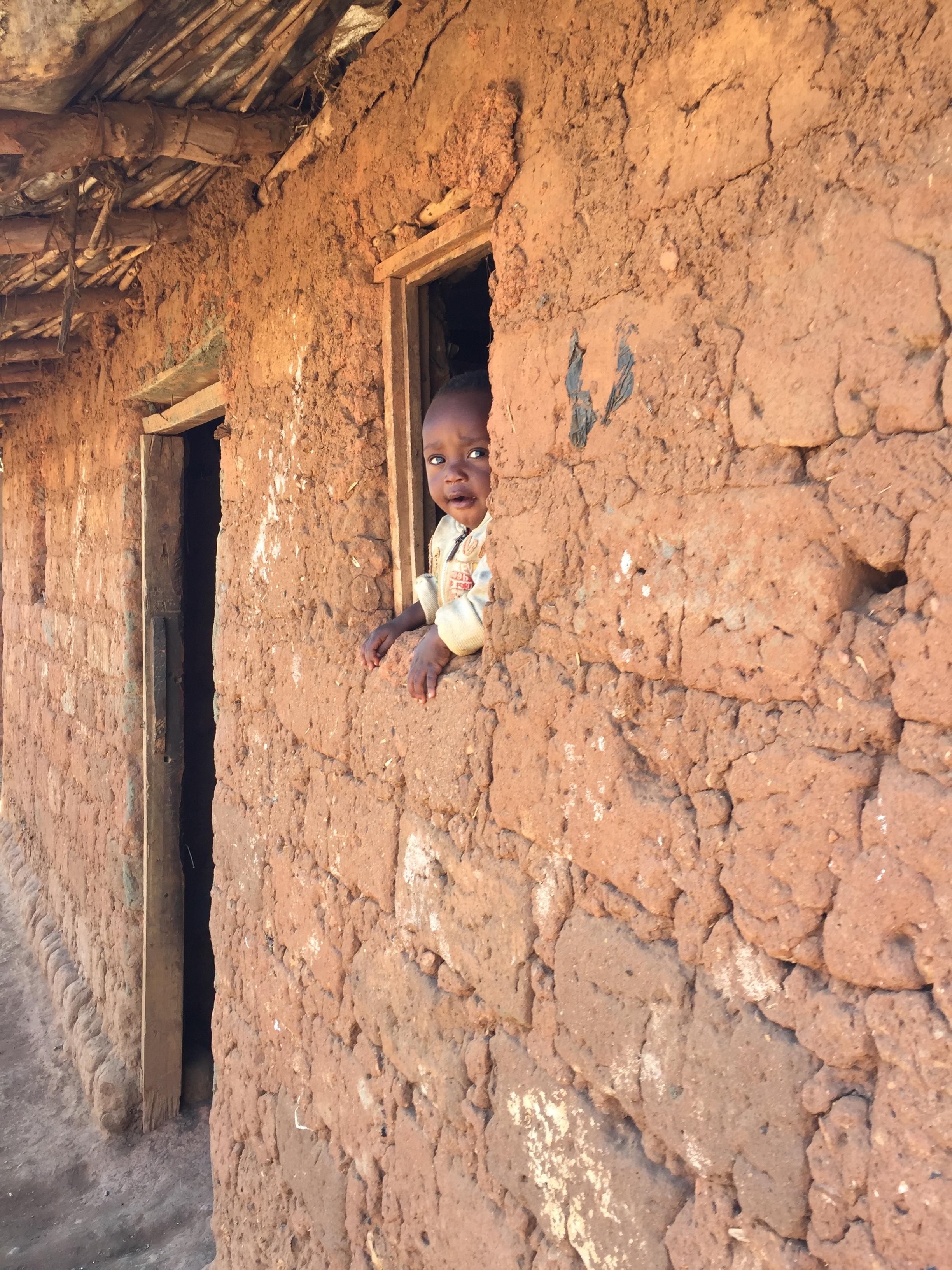 A child in a self-built mud hut