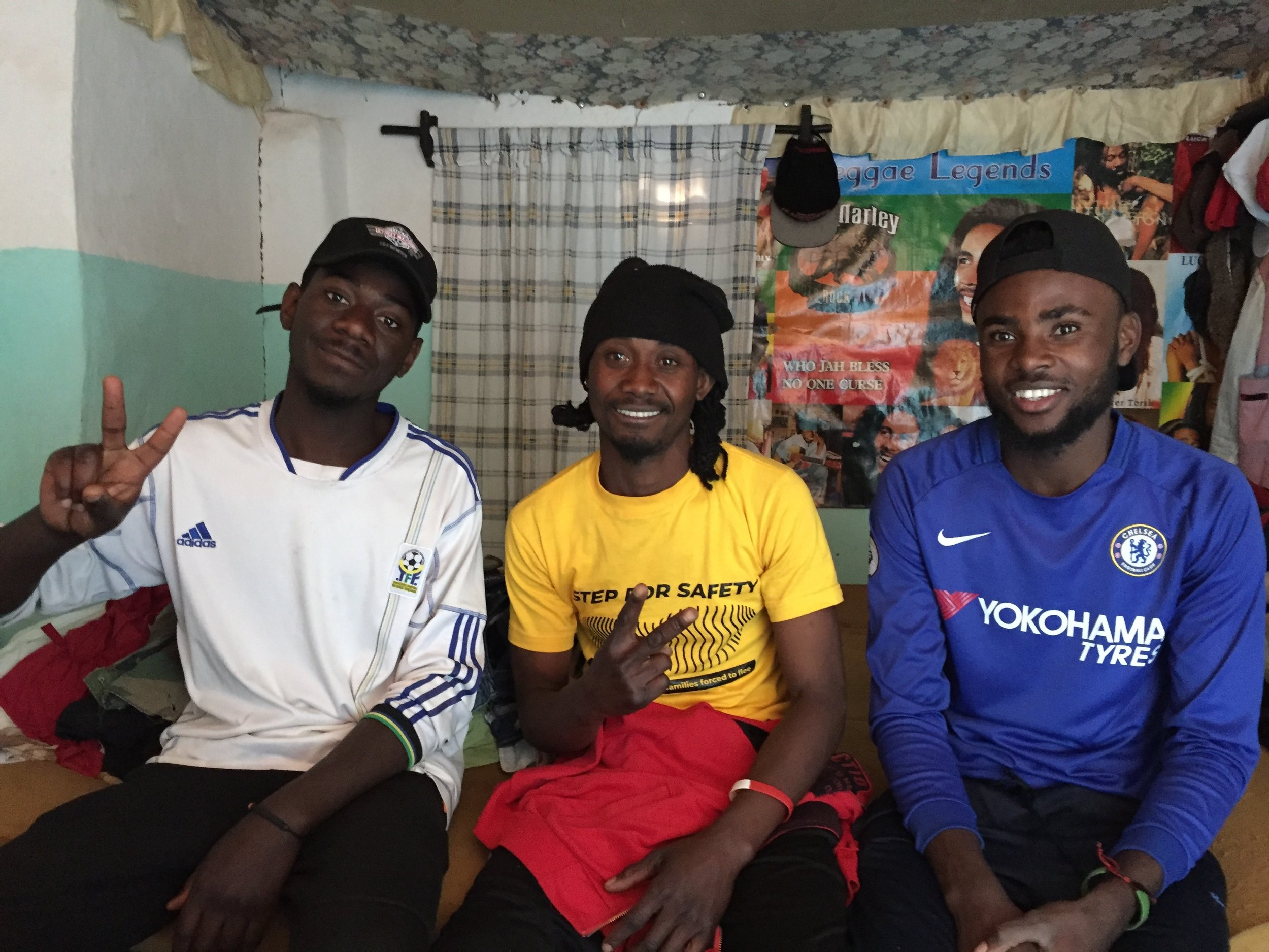 Edmund (left) is from the DRC. He has been in the camp for 14 years and has just finished his diploma. Dan (right), also from the DRC and a refugee at the camp for 14 years. Simple Jay (centre) is the camp's tattooist. He uses a stick & poke method, using a needle and ink that's stored in a syringe for safe keeping. Customers come to him to have mostly animals and names of loved ones tattooed. He is a Rasta and fashioned a key out of a stick for his hut's door—he called it a Rasta key. He is also in the camp's dance troop.