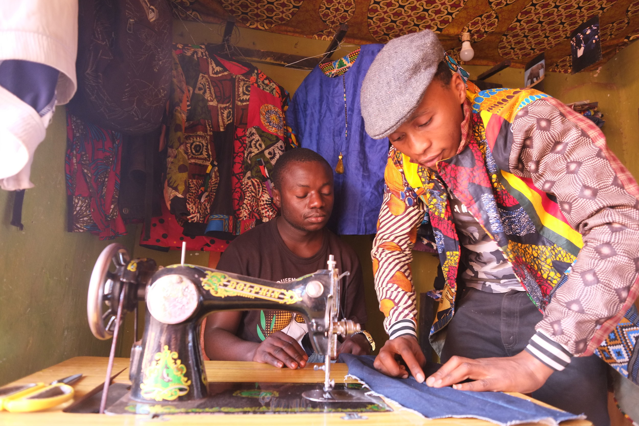 Shalex (right) makes and sells clothing at the camp. He also runs workshops teaching other refugees how to sew.