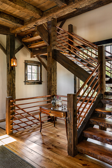A stairway designed by Crisp Architects with reclaimed wood and copper pipes.